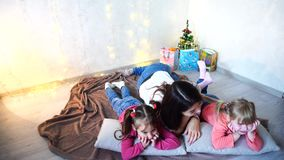 Leuke vrouwelijke en twee voor camera stellen en meisjeskinderen die, die die op kussens, op vloer in ruimte liggen met glimlache stock footage