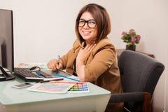 Leuke vrouwelijke ontwerper in een bureau Stock Foto's
