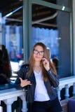 Leuke vrouwelijke persoon die glazen dragen en door smartphone bij straatkoffie spreken Royalty-vrije Stock Afbeelding