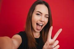 Leuke vrouwenjaren '20 in zwarte t-shirt die pret hebben en selfie verstand nemen Stock Fotografie