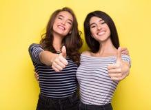 Leuke vrouwenvrienden die duimen op gele achtergrond tonen stock foto