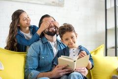 leuke weinig dochter sluitende ogen aan gelukkige vader terwijl vader en zoons de lezing op bank boekt stock afbeeldingen
