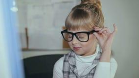 Leuke weinig, glimlachend meisje in glazen werkt gewillig met PC in bureau 4K stock videobeelden