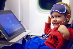 Leuke weinig jong geitje het letten op beeldverhalen tijdens de lange vlucht in vliegtuig Stock Foto