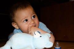Leuke zes maanden oud babyjongen het spelen met blauwe teddybeer op de vloer, het tandjes krijgen en het vroege ontwikkelingsconc stock afbeeldingen