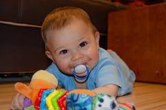Leuke zes maanden oud babyjongen het spelen op Flor met tandjes krijgenstuk speelgoed, vroeg ontwikkeling en tandjes krijgenconce stock afbeelding