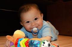 Leuke zes maanden oud babyjongen het spelen op Flor met tandjes krijgenstuk speelgoed, vroeg ontwikkeling en tandjes krijgenconce stock afbeeldingen