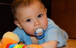Leuke zes maanden oud babyjongen het spelen op Flor met tandjes krijgenstuk speelgoed, vroeg ontwikkeling en tandjes krijgenconce royalty-vrije stock foto