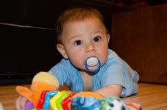 Leuke zes maanden oud babyjongen het spelen op Flor met tandjes krijgenstuk speelgoed, vroeg ontwikkeling en tandjes krijgenconce royalty-vrije stock fotografie