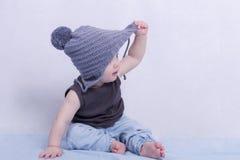 Leuke zuigelingsjongen in een grijze hoed en het proberen om het weg te nemen Royalty-vrije Stock Afbeelding