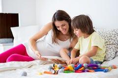 Leuke zwangere moeder en kindjongen die samen binnen spelen stock afbeeldingen