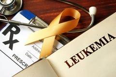 Leukemia written on a page. And  orange awareness ribbon Royalty Free Stock Photos