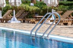 Leuningen door de pool met blauw water tegen de zonlanterfanters en de gevouwen paraplu's stock afbeeldingen