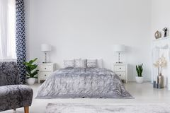 Leunstoel en installaties in wit elegant slaapkamerbinnenland met bed tussen kabinetten met lampen Echte foto stock afbeeldingen