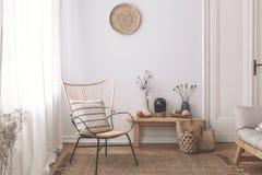 Leunstoel met hoofdkussen op bruine deken in wit natuurlijk woonkamerbinnenland met installaties Echte foto stock afbeeldingen