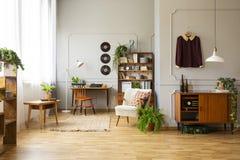 Leunstoel naast installatie in uitstekend woonkamerbinnenland met houten kabinet en stoel bij bureau Echte foto royalty-vrije stock afbeeldingen