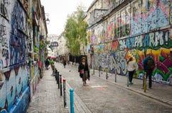Leute überschreiten durch die azzling Straßenkunst auf Rue Denoyez in Paris Lizenzfreie Stockbilder
