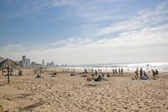 Leute auf Addington-Strand gegen Stadt-Skyline Stockbilder