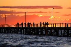 Leute auf Anlegestelle-überwachendem Sonnenuntergang Stockbild