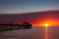 Leute auf Anlegestelle bei Sonnenuntergang Stockfotos