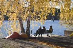 Leute auf Bank durch das Wasser, gestaltet in den schönen Herbstfarben Lizenzfreie Stockfotos