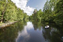Leute auf dem Boot, das in den Teich schwimmt Stockbilder