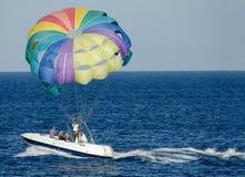 Leute auf dem Boot legten bunten mehrfarbigen Fallschirm frei Stockbild