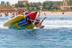 Leute auf dem bunten Bananenboot, das auf das Wasser mit Spritzwasser schwimmt Stockbild