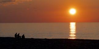 Leute auf dem Hintergrund des Sonnenuntergangs und das Meer auf der Ufergegend lizenzfreies stockbild