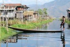 Leute auf dem Rudern eines Bootes am Dorf von Maing Thauk stockbild