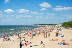 Leute auf dem sonnigen Strand von Ostsee Lizenzfreie Stockbilder