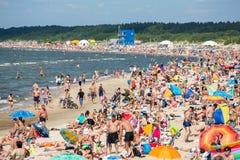 Leute auf dem sonnigen Strand von Ostsee Lizenzfreies Stockbild