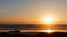 Leute auf dem Strand am Sonnenuntergang stockfotografie