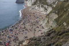 Leute auf dem Strand und den weißen Klippen von Durdle-Tür Stockbilder