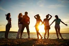 Leute auf dem Strandsonnenuntergang Stockbild
