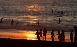 Leute auf dem Strandsonnenuntergang Lizenzfreie Stockfotos