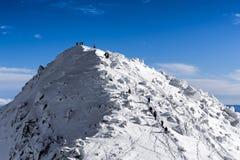 Leute auf den Hügel des verschneiten Winters Stockfotos