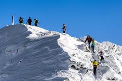 Leute auf den Hügel des verschneiten Winters Stockfotografie
