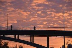 Leute auf der Brücke in der Sonnenuntergangzeit Stockbild