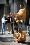 Leute auf der Köln-Straße, welche die magischen indischen Künstler in der orange Kleidung betrachtet Lizenzfreie Stockfotografie