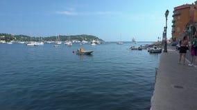 Leute auf der Promenade und dem blauen Wasser im Villefranche-sur-Mer stock video footage