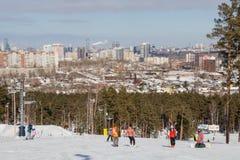 Leute auf der Skisteigung und der Ansicht der Stadt von Jekaterinburg stockbild