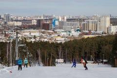 Leute auf der Skisteigung und der Ansicht der Stadt von Jekaterinburg stockbilder