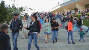 Leute auf der Treppe und dem Gras an der Stadt parken am Volksfestivalherzen von Eurasien stock video