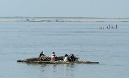 Leute auf einem Floss mit dem Bauholz, das auf dem Fluss Ayeyarwady kreuzt Lizenzfreie Stockfotos