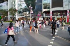 Leute auf einem Fußgängerübergang auf Obstgarten-Straße Stockbild