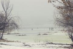 Leute auf einem leeren Frühlingsstrand auf einer Flussbank unter Bäumen nebelig stockfoto
