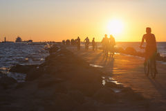Leute auf Fahrrädern reiten entlang den Graben im Meer bei Sonnenuntergang lizenzfreie stockbilder