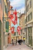 Leute auf Fußgängerstraße mit Flaggen auf Altbauten in Zuric Stockfotografie