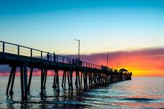 Leute auf Pier am Sonnenuntergang Stockfotos